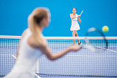 Wide angle portrait of two female players playing tennis in indoor court, focus on woman in back, copy space