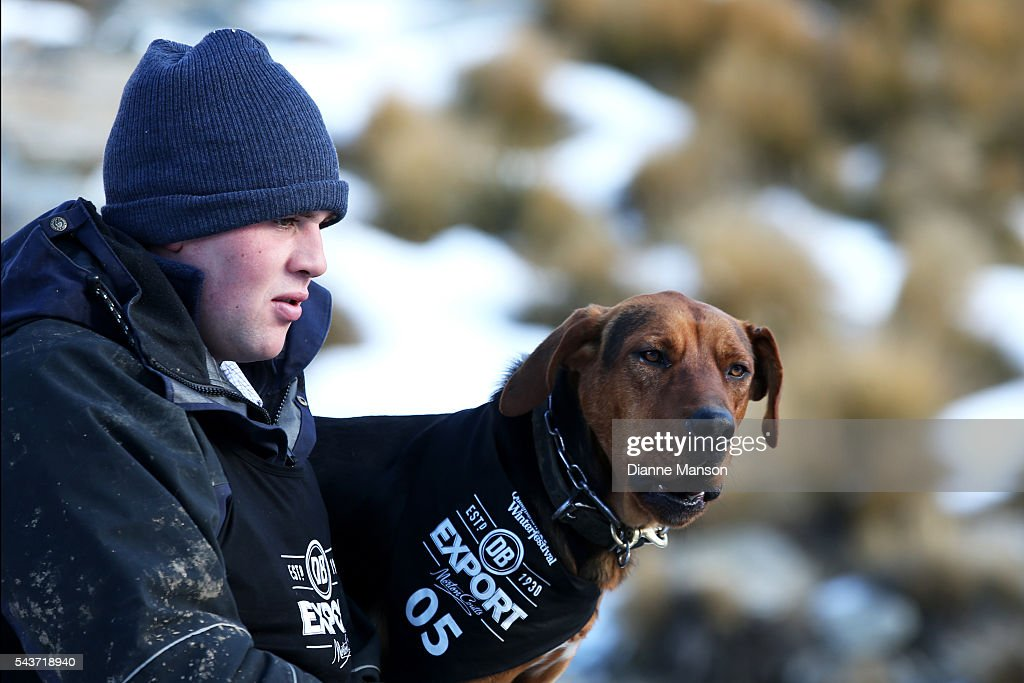 A competitor and his dog look on prior to the start of the DB Export Dog Derby at the Remarkables ski field on June 30, 2016 in Queenstown, New Zealand.