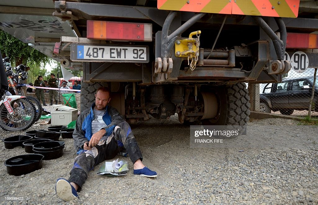 A competitor checks his phone under a truck in Cachi after the Stage 7 of the Dakar Rally 2013 between Calama and Salta, Argentina, on January 11, 2013. The rally takes place in Peru, Argentina and Chile January 5-20.