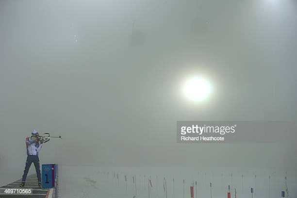 A competitor checks the visibilty through his rifle sights before the competion was postponed due to fog before the Men's 15 km Mass Start during day...