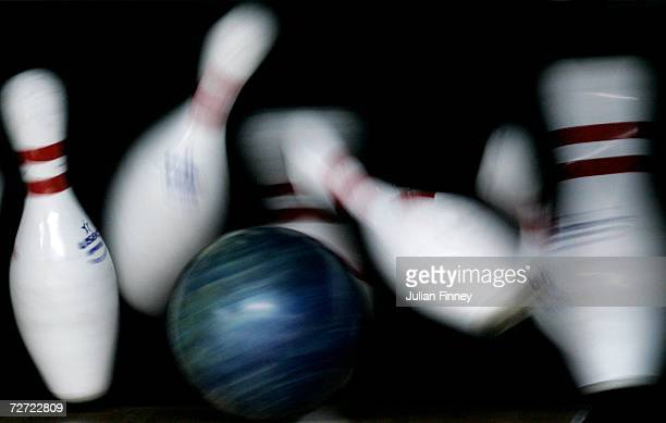 A competitor clears the pins to score a strike during the Men's Trios 3 games Squad B 1st Block Bowling Competition at the Qatar Bowling Centre...