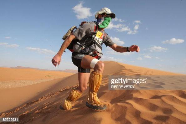 A competitor climbs a dune during the third stage of the 24rd Marathon des Sables in the Sahara desert some 300 kilometers south of Ouarzazate on...