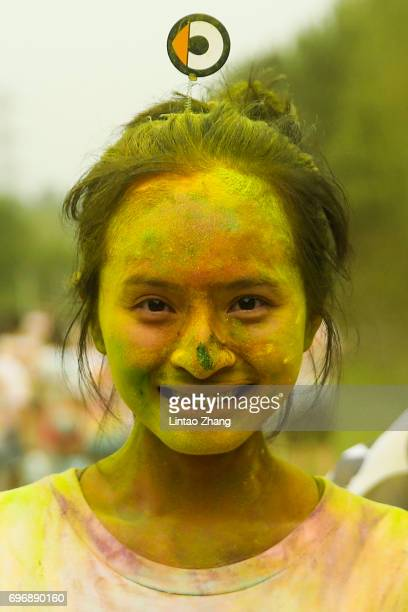 A competitor covered in coloured powder poses after finishing the Color Run at the Beijing International Garden Expo park on June 17 2017 in Beijing...