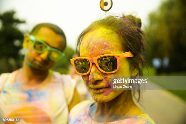 Competitor covered in coloured powder poses after finishing the Color Run at the Beijing International Garden Expo park on June 17 2017 in Beijing...