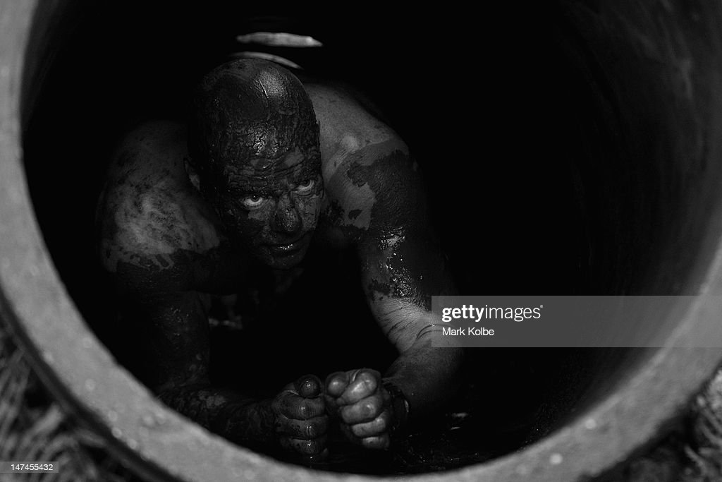 A competitor crawls through a concrete pipe in 'Goldmine' obstacle as he competes in the Tough Bloke Challenge at the Cataract Scout Park on June 30, 2012 in Sydney, Australia.