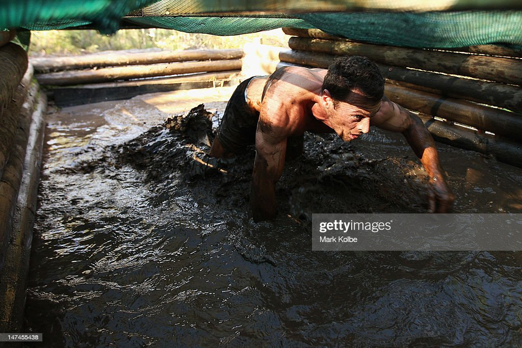 A competitor crawls through the 'Alligator Pit' obstacle as he competes in the Tough Bloke Challenge at the Cataract Scout Park on June 30, 2012 in Sydney, Australia.