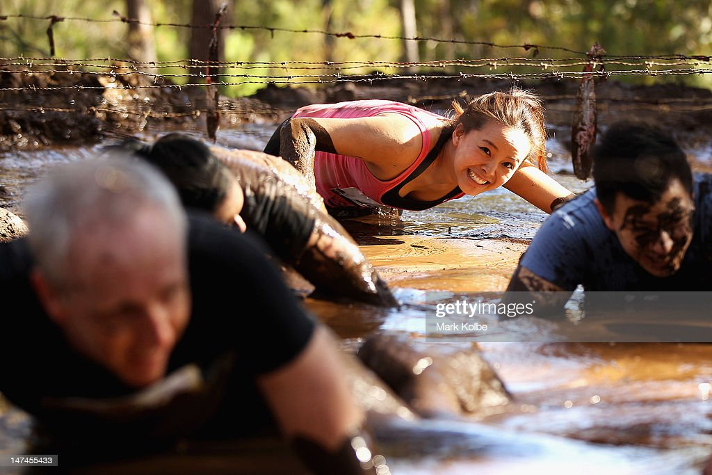 A competitor crawls through the 'Mud Bath' obstacle as she competes in the Tough Bloke Challenge at the Cataract Scout Park on June 30, 2012 in Sydney, Australia.