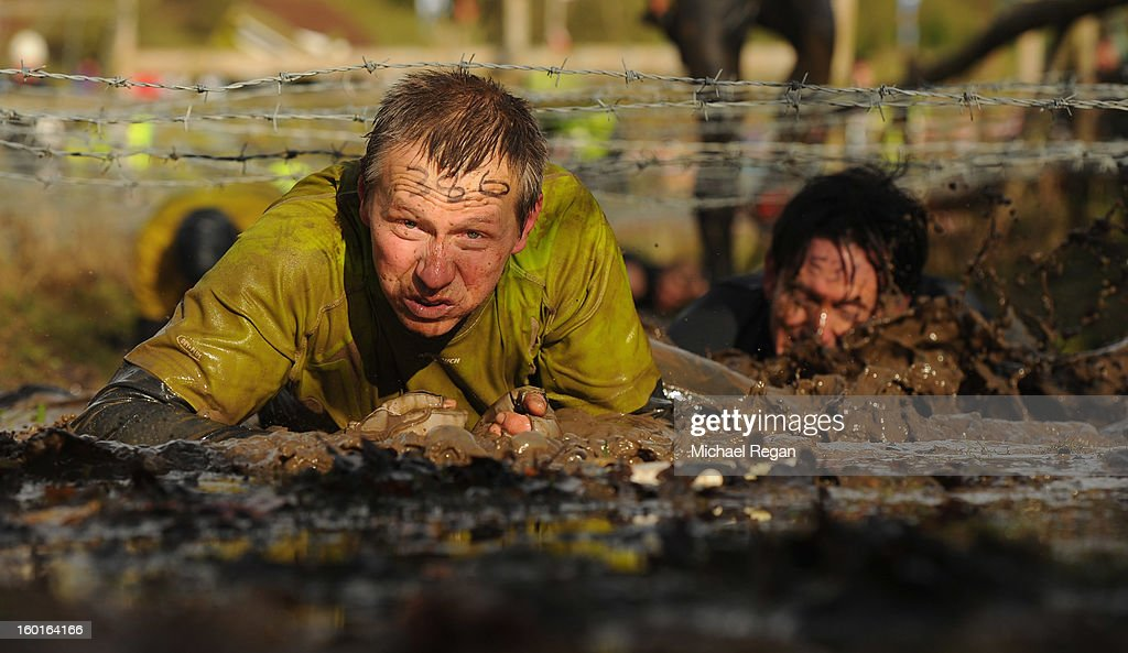 A competitor crawls under barbed wire during the Tough Guy Challenge endurance race on January 27, 2013 in Telford, England. Every year thousands of people run the 8 mile assault course which involves freezing temperatures, fire and ice.