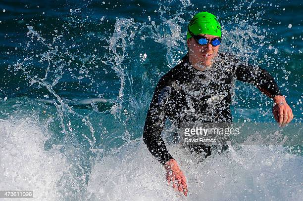 A competitor dives into the sea ahead of the Ironman 703 race on May 16 2015 in Barcelona Spain
