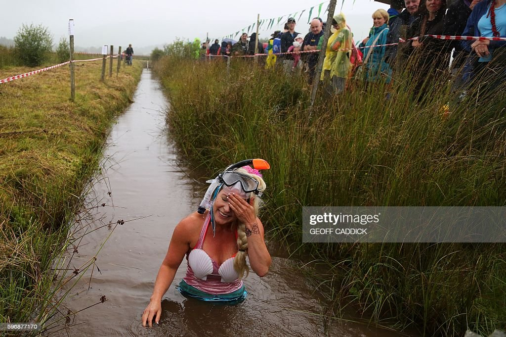 A competitor dressed as a mermaid wipes her brow as she completes the course during the World Bog Snorkelling Championships in Waen Rhydd peat bog at...