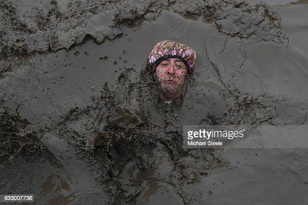 A competitor falls backwards into muddy waters during the Tough Guy Challenge at South Perton Farm on January 29 2017 in Telford England