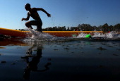 A competitor finishes the swim leg in the Mens Triathlon during day three of the 2013 Australian Youth Olympic Festival at the Sydney International...