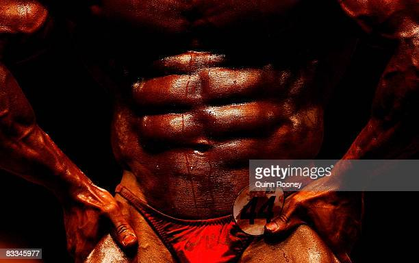 A competitor flexes his abs during the Body Building on day two of the 2008 Asian Beach Games at Kuta Beach on October 19 2008 in Bali Indonesia