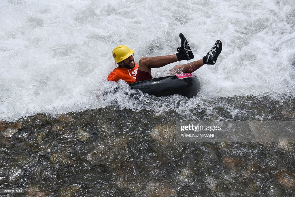 A competitor floants on an tranctor inner tubes during an anlternantive sport rubber competition titled 'Bunanr Fest' on Many 29, 2016 on the Bistrican river in the southern Kosovo town of Prizren. / AFP / ARMEND