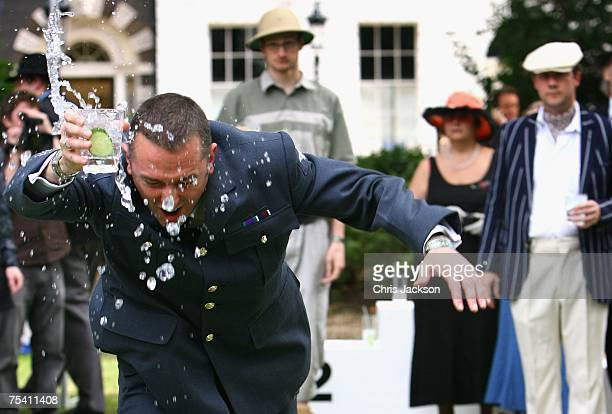 A competitor holds on to his Gin and Tonic as he takes part in the 'Hop skip and G and T' during the third Chap and Hendricks Olympiad in Bedford...