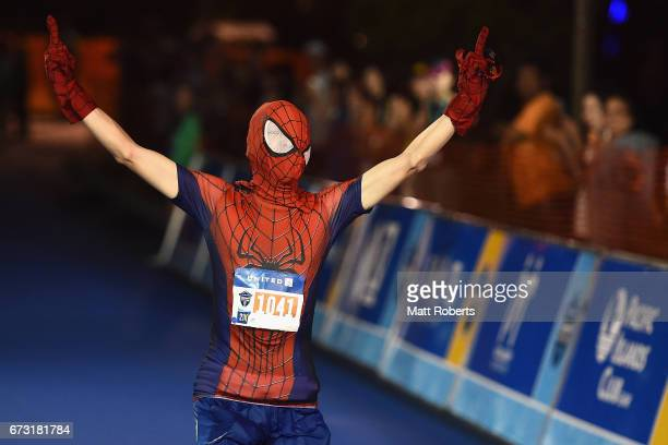 A competitor in a Spiderman costume runs down to the finish during the United Airlines Guam Marathon 2017 on April 9 2017 in Guam Guam