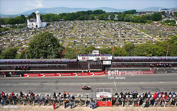 A competitor in the centenary Isle of Man TT superbike race passes the startfinish line at Douglas with the cemetery behind where many riders who...