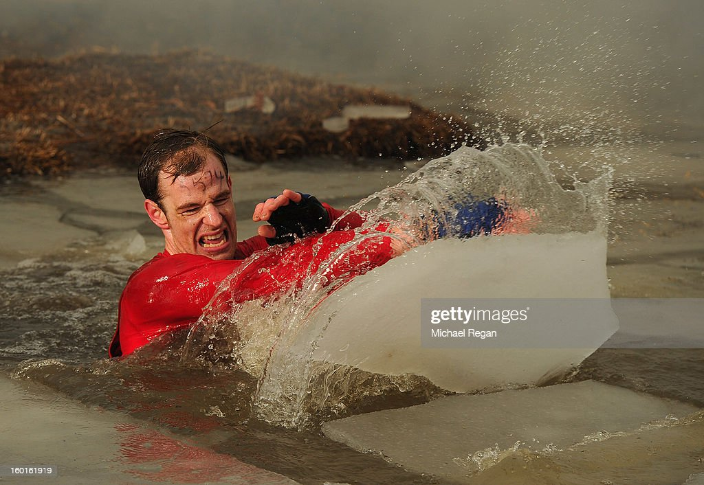 A competitor moves ice from his way as he wades through muddy water during the Tough Guy Challenge endurance race on January 27, 2013 in Telford, England. Every year thousands of people run the 8 mile assault course which involves freezing temperatures, fire and ice.