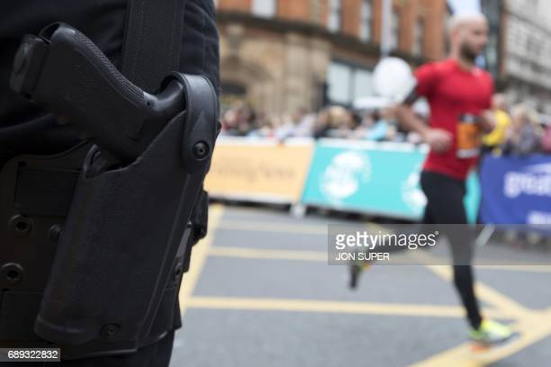 A competitor passes an armed policeman at the start of the Great Manchester Run in Manchester north west England on May 28 2017 Britain police have...