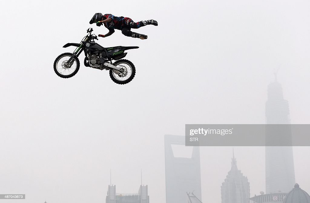 A competitor performs an extreme motocross jump with the Shanghai skyline from the historic Bund area in Shanghai on April 27, 2014, to kick off the Kia World Extreme Games. The games will highlights nearly 200 of the best action sport athletes from almost 30 countries and regions, competing in BMX freestyle, aggressive in-line, skateboarding, speed climbing and international freestyle motocross competition. CHINA