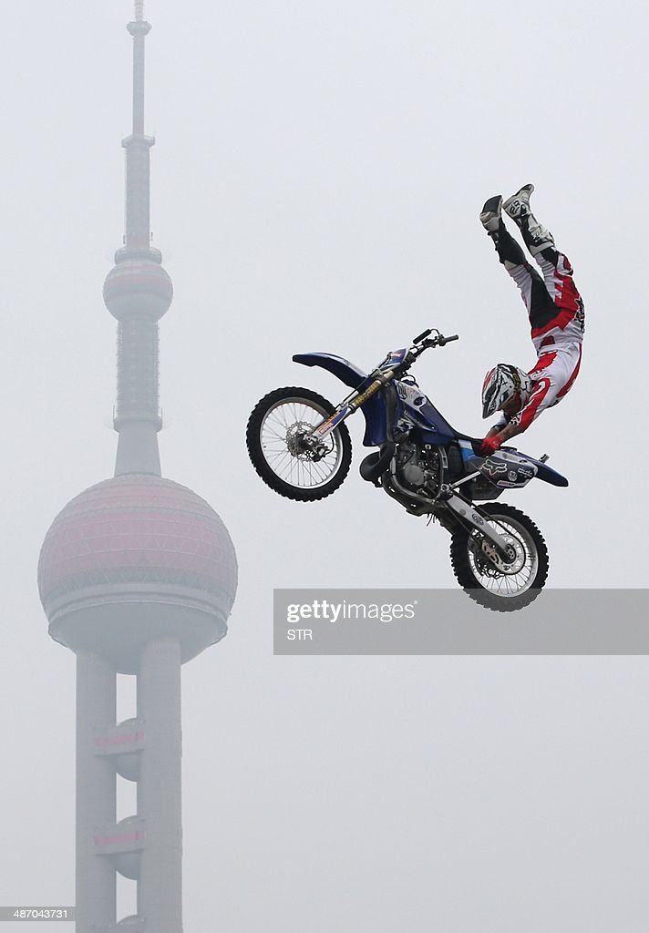 A competitor performs an extreme motocross jump with the Shanghai skyline from the historic Bund area in Shanghai on April 27, 2014, to kick off the Kia World Extreme Games. The games will highlights nearly 200 of the best action sport athletes from almost 30 countries and regions, competing in BMX freestyle, aggressive in-line, skateboarding, speed climbing and international freestyle motocross competition. CHINA OUT AFP PHOTO