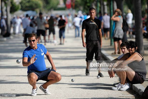 PRATABUY A competitor plays boules as others look on on July 3 2011 at the Borely park in Marseille southern France during the 50th world...