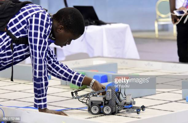 A competitor prepares a robot during the final of the national robotics competition on May 20 2017 at the Marius Ndaye stadium in the Senegalese...