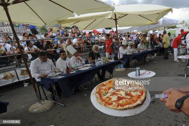 A competitor presents his pizza Margherita during the 13th edition of the Pizza makers World Championships in Naples on September 3 2014 AFP...