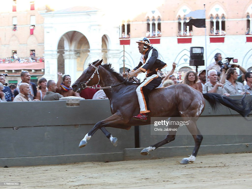 A Competitor races on horseback across the Piazza del Campo square during the annual Palio dell'Assunta horse-race on August 16, 2013 in Siena, Italy. The horse of the Contrada della Lupa with jockey Jonatan Bartoletti leads at this moment. The Palio races in Siena, in which riders representing city districts compete,and takes place twice a year in the summer in a tradition that dates back to 1656.