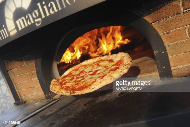 A competitor removes his pizza from the oven during the 2014 Pizza makers World Championships in Naples on September 3 2014 AFP PHOTO/MARIO LAPORTA
