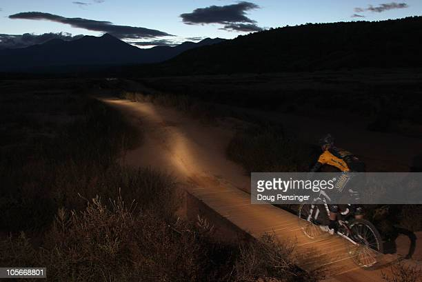 A competitor rides into the sunrise during the 24 Hours of Moab Mountain Bike Race on October 10 2010 in Moab Utah More than 1000 mountain bikers...