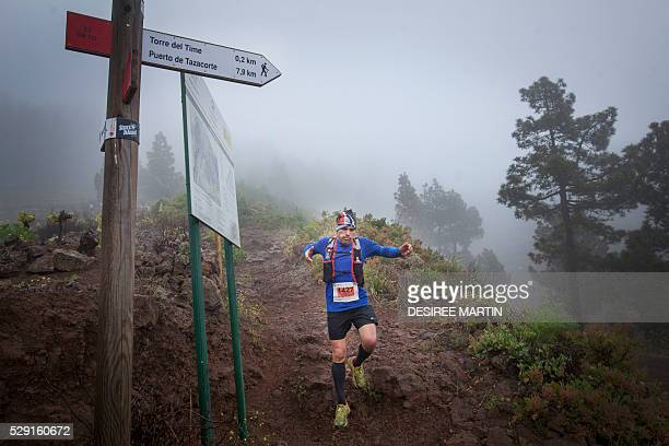 A competitor runs down a track though foggy vineyards in the Caldera de Taburiente National Park during the Transvulcania ultra trail event on May 7...