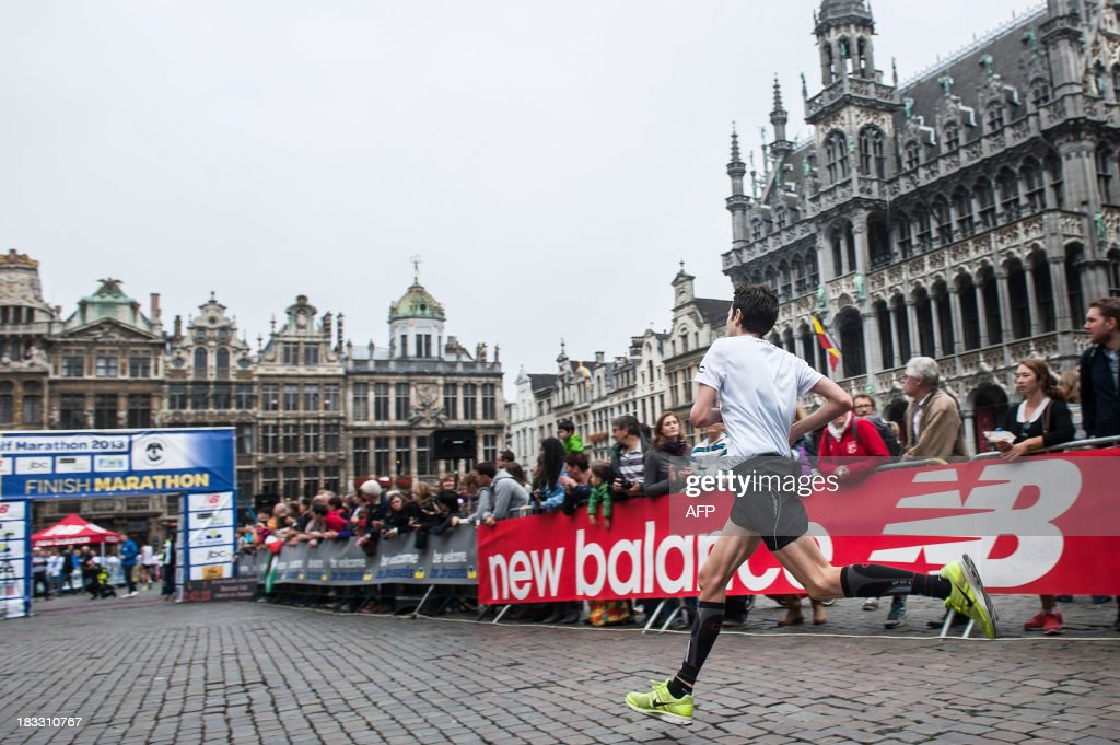 A competitor runs on the Grand Place (Grote Markt), in front of the Brussels city hall, to cross the finish line during the tenth edition of the Brussels marathon, on October 6,2013.