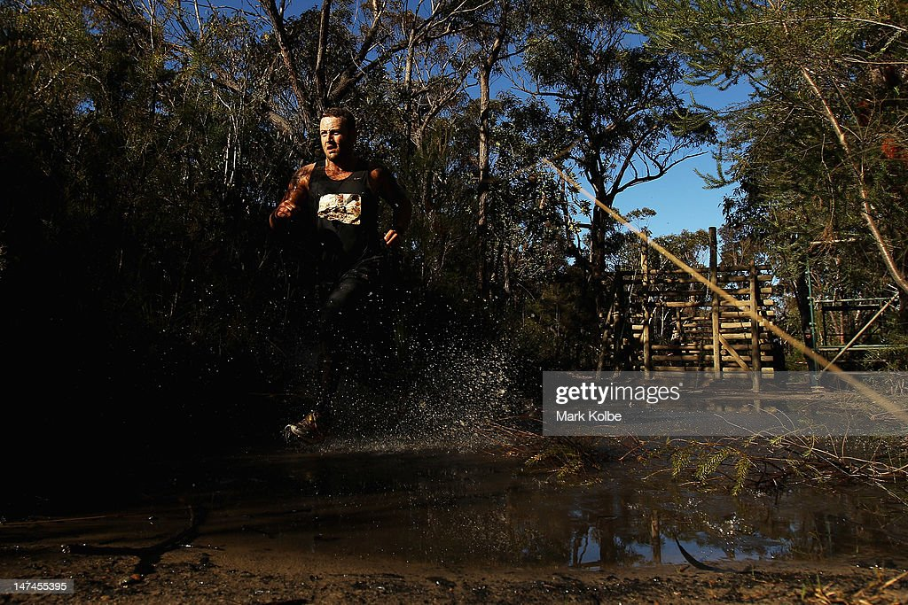 A competitor runs through a puddle as he competes in the Tough Bloke Challenge at the Cataract Scout Park on June 30, 2012 in Sydney, Australia.