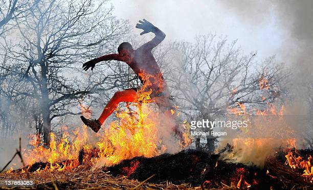 A competitor runs through fire during the Tough Guy Challenge endurance race on January 29 2012 in Telford England Every year thousands of people run...