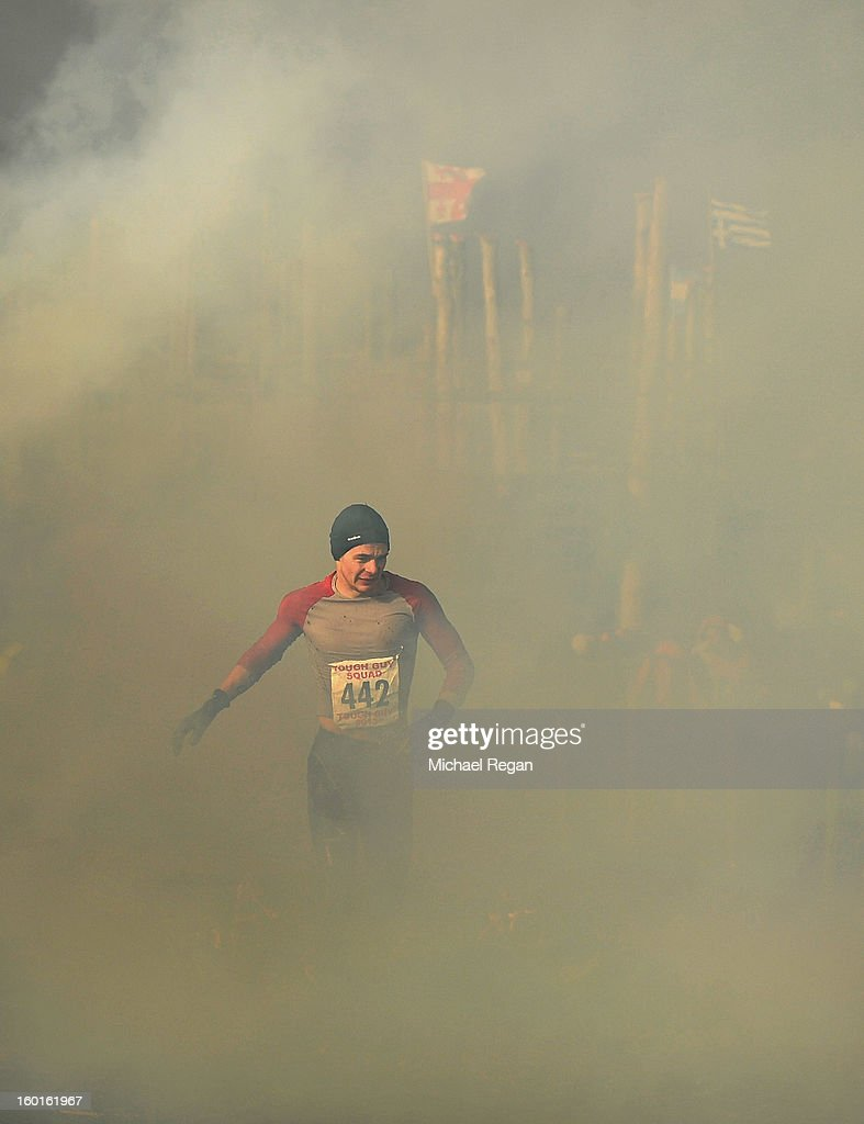 A competitor runs through smoke during the Tough Guy Challenge endurance race on January 27, 2013 in Telford, England. Every year thousands of people run the 8 mile assault course which involves freezing temperatures, fire and ice.