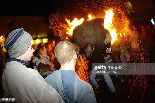 A competitor runs with a wooden barrel filled with burning tar 05 November 2004 in Ottery St Mary Britain Every year the village of Ottery St Mary in...