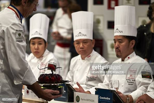 A competitor shows his creation to members of the jury during the Pastries World Cup final on January 22 2017 in Chassieu outside Lyon as part of the...