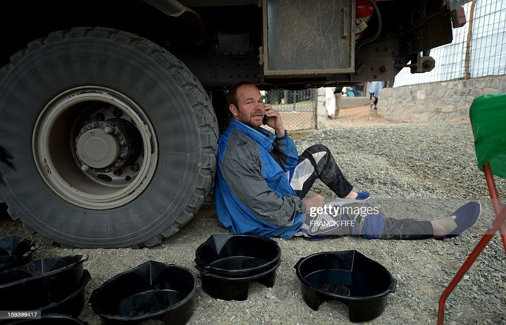 A competitor speaks on the phone under a truck in Cachi after the Stage 7 of the Dakar Rally 2013 between Calama and Salta, Argentina, on January 11, 2013. The rally takes place in Peru, Argentina and Chile January 5-20.