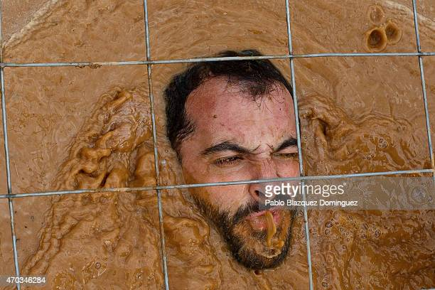 A competitor spits water as he passes under a fence through the water during the first Belik Race on April 19 2015 in Cabanillas del Campo in the...