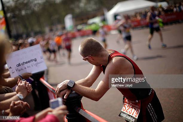 A competitor stretches off on the sidelines during the Virgin London Marathon 200m from the finish line on April 17 2011 in London England 36500...