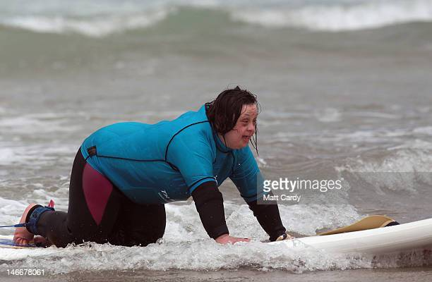 A competitor takes part in a heat during the UK's first ever surfing competition exclusively for people with learning disabilities at Fistral Beach...