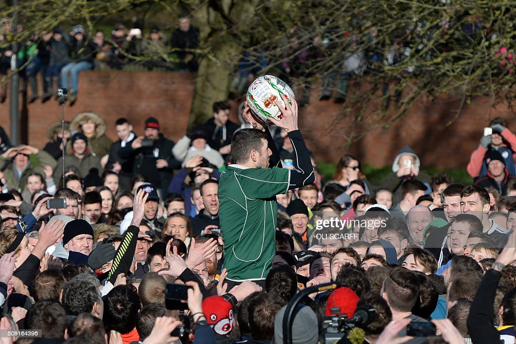 A competitor takes possession of the ball as from the opposing teams, the Up'ards and the Down'ards, take part in the annual Royal Shrovetide Football Match in Ashbourne, northern England, on February 9, 2016. The mass-participation ball game involves two teams, whose players are defined by which side of a small brook that bisects the town they were born, aiming to score a goal, which are some three miles apart. The game, which has very few rules, is played over two 8 hour periods on Shrove Tuesday and Ash Wednesday. Royal Shrovetide Football is believed to have been played annually in Ashbourne since 1667. / AFP / OLI SCARFF