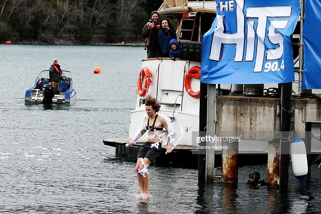 A competitor tarred and feathered dives off the wharf during the American Express Queenstown Winter Festival Hits 90.4 Birdman competition on June 26, 2016 in Queenstown, New Zealand.
