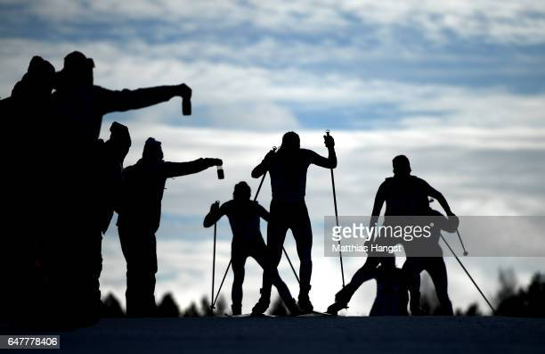 Competitors are offered drinks as they compete in the Women's Cross Country Mass Start during the FIS Nordic World Ski Championships on March 4 2017...