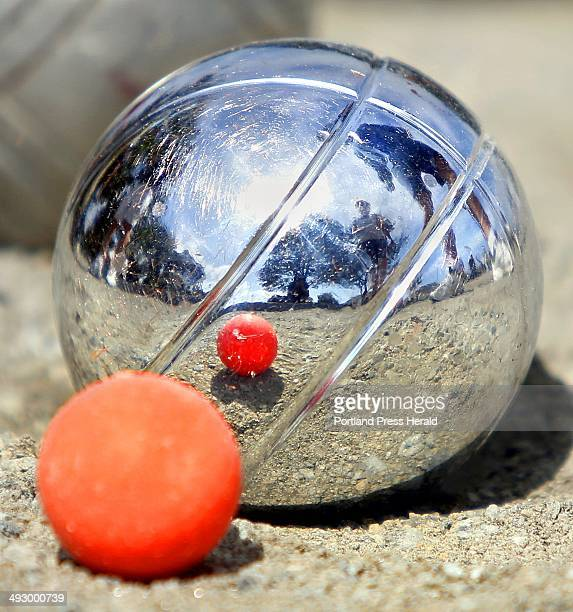 Competitors are reflected off a steel ball called a boule as they determine whose ball is closest to the orange ball called a piglet during the Old...