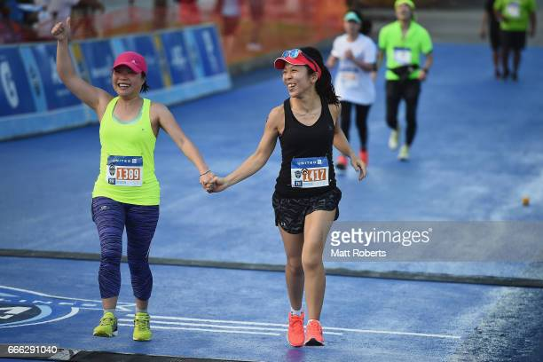 Competitors celebrate as they cross the finish of the 10 km during the United Airlines Guam Marathon 2017 on April 9 2017 in Guam Guam