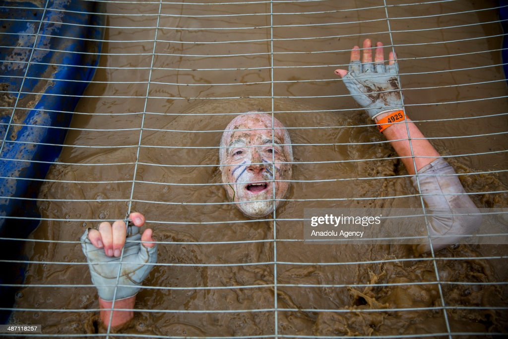 Competitors crawl in a cage filled with muddy water while challenging in Tough Mudder endurance race in Henley-on-Thames, England on 27 April, 2014. Competitors run a 19km course, designed by British Special Forces to test competitors' strength, stamina, mental grit, and camaraderie with mud and obstacles that play on common human fears, such as fire, water, electricity and heights.