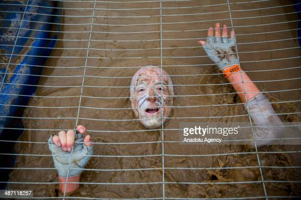 Competitors crawl in a cage filled with muddy water while challenging in Tough Mudder endurance race in HenleyonThames England on 27 April 2014...