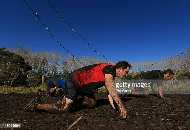 Competitors crawl under barbed wire during the Tough Guy and Gal Challenge at Woodhill Sands on July 8 2012 in Auckland New Zealand